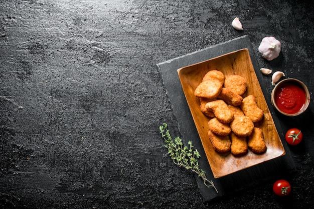 黒い素朴なテーブルの上のソース、タイム、ニンニクとプレート上のチキンナゲット