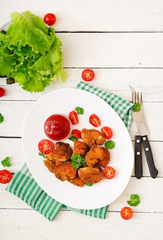 Chicken nuggets and sauce in plate on a white wooden table