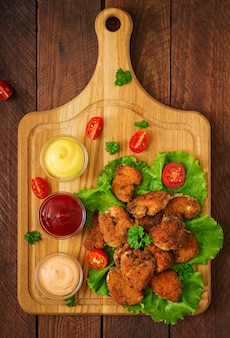 Chicken nuggets and sauce on a wooden table