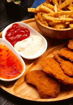 Chicken nuggets served with french fries, ketchup and mayonnaise on wooden board