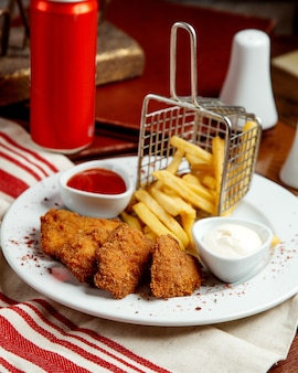 Chicken nuggets served with french fries mayonnaise and ketchup