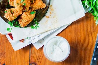 鶏のナゲット、デリケートなニンニクディップ、木製のテーブル