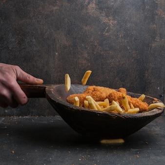 Bocconcini di pollo con patatine fritte e mano umana nel piatto di legno