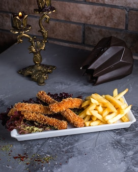 Куриные наггетсы с картофелем фри на столе