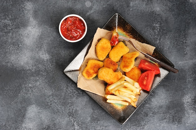 Chicken nuggets with french fries, tomato ketchup