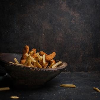 Bocconcini di pollo con patatine fritte nel piatto di legno
