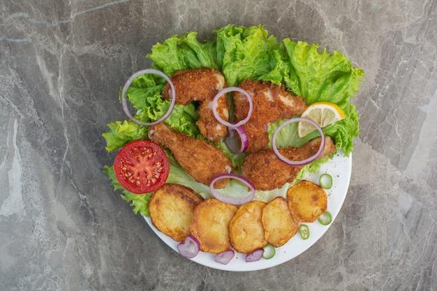 Pepite di pollo con patate fritte e cipolla sul piatto bianco.