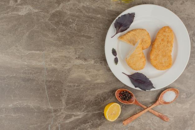 Pepite di pollo con foglia, limone, cucchiaio sul piatto bianco.