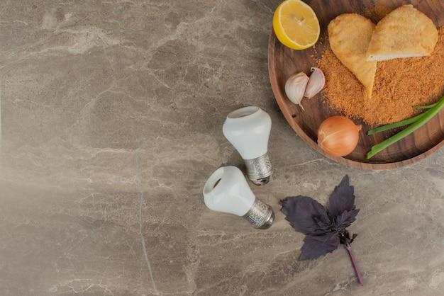 Куриные наггетсы с лимоном, двумя чесноками и луком на деревянной доске с солью и перцем.