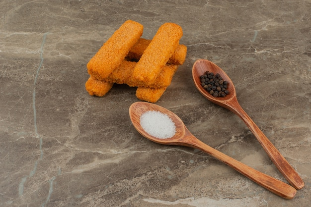Bocconcini di pollo con un cucchiaio di sale e pepe.
