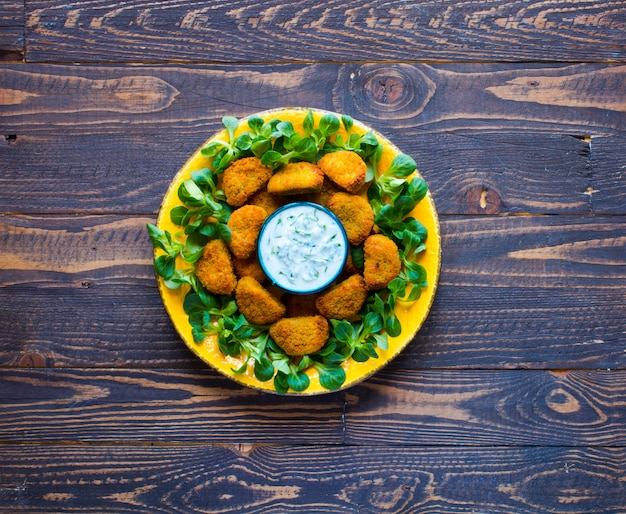 Chicken nuggets with yogurt sauce on a wooden background