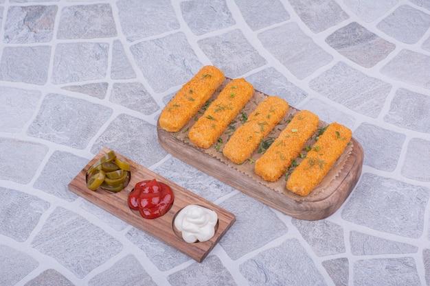 Pepite di pollo su tavola di legno con salse.