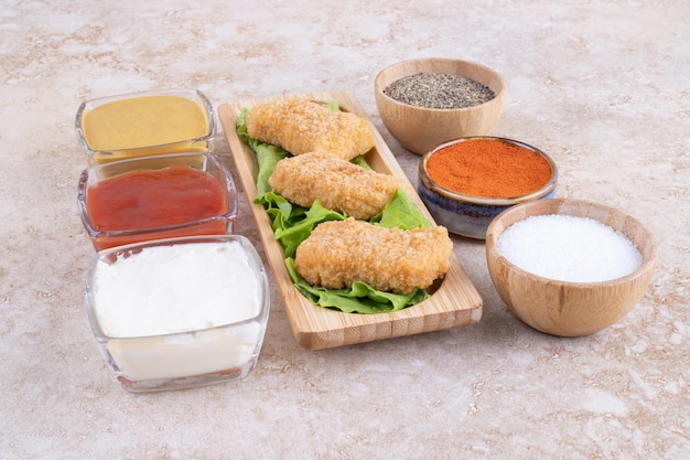 Chicken nuggets on a wooden board with variety of sauces around.