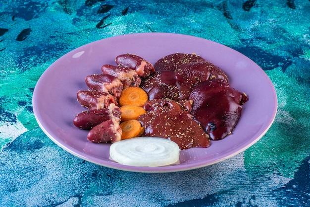 Куриные субпродукты, морковь и лук на тарелке
