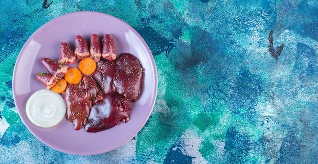 鶏内臓、にんじん、玉ねぎを皿に盛り付けます