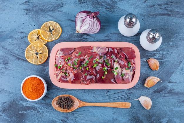 Куриные субпродукты в деревянной тарелке, специи, соль, специи с ложкой чеснока и сушеного лимона, на синем.