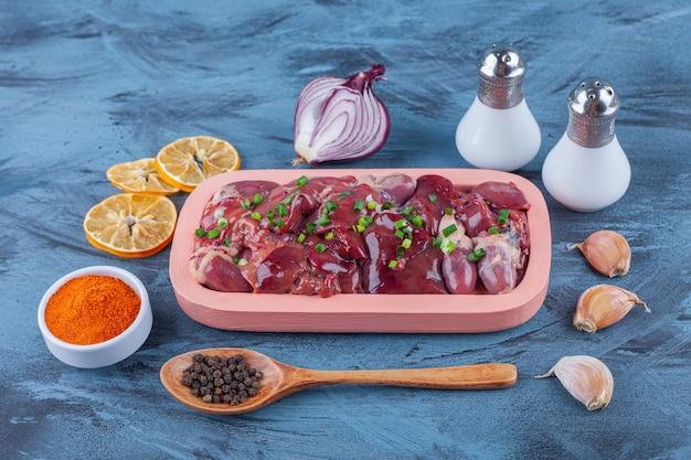 Frattaglie di pollo in un piatto di legno, spezie, sale, spezie con un cucchiaio di aglio e limone essiccato sulla superficie blu