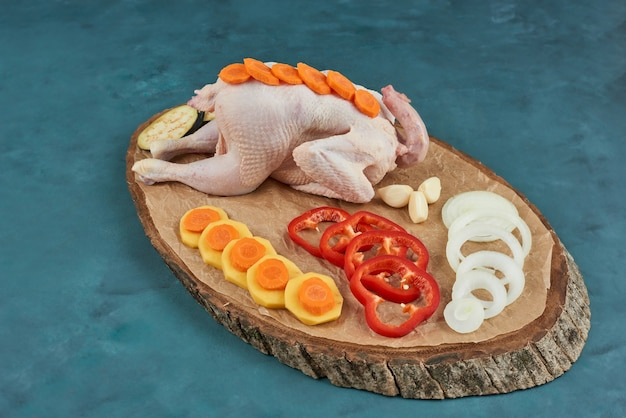 Курица на деревянной доске с овощами вокруг.