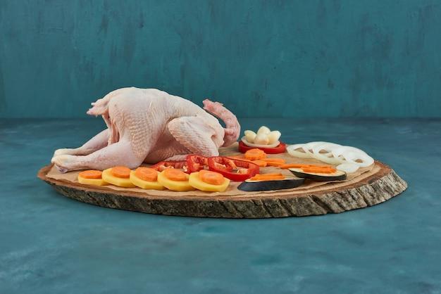 周りに野菜と木の板に鶏肉。