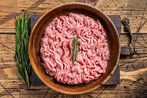 닭고기 또는 칠면조 고기, 나무 접시에 원시 가금류. 나무 테이블. 평면도.