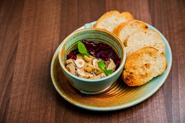 구운 빵과 함께 제공되는 비트와 견과류 조림을 곁들인 치킨 페이스트 또는 페이트