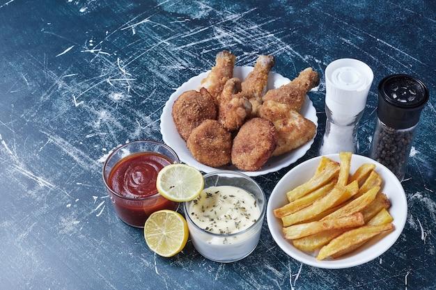 白い皿にジャガイモを添えた鶏肉。