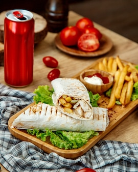 Chicken pita roll and french fries on a wooden board