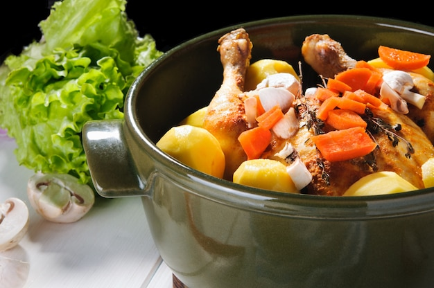 Chicken, potato and carrot with other vegetables in round ceramic pot on white wooden table