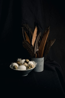 Pollo e uova di quaglia tra le piume in una ciotola vicino a grandi acule in lattina