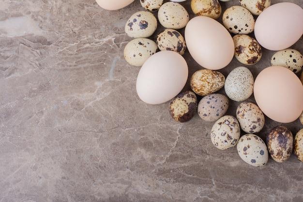 Pollo e uova di quaglia su marmo.