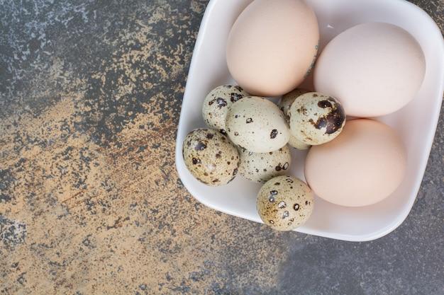 Pollo e uova di quaglia sulla ciotola bianca.