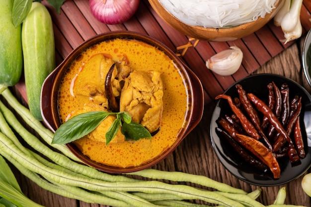 말린 고추, 바질, 오이, 긴 콩을 넣은 그릇에 치킨 레드 카레