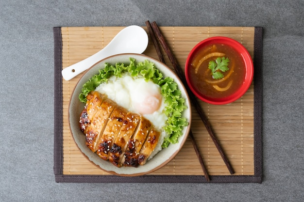Курица с рисом или терияки с курицей и яйцом онсэн в серой миске с устричным соусом на столе.