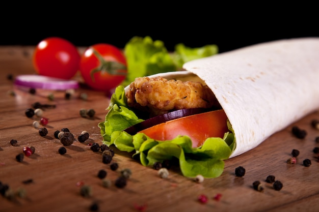 Chicken roll with lettuce tomato onion and pepper on a wooden table and black background.