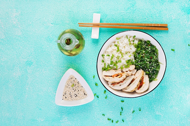 Chicken rolls, rice, chuka and green onion in white bowl with chopsticks