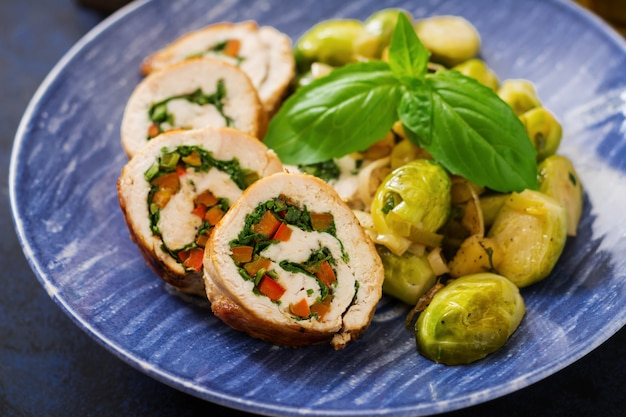 Куриные рулетики с зеленью, украшенные тушеной брюссельской капустой, яблоками и луком-пореем на синей тарелке.