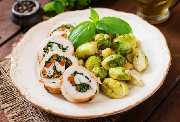 Куриные рулетики с зеленью, украшенные тушеной брюссельской капустой, яблоками и луком-пореем на тарелке.
