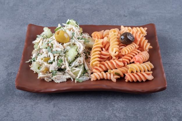 Куриный салат и макаронные изделия фузилли на коричневой тарелке.
