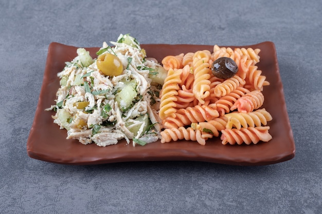 Chicken salad and fusilli pasta on brown plate.
