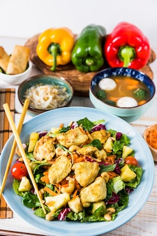 Chicken salad with chopsticks; beans sprout and fish ball soup on table