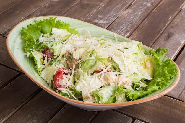 나무 테이블에 빙산 양상추와 크루통을 곁들인 치킨 샐러드