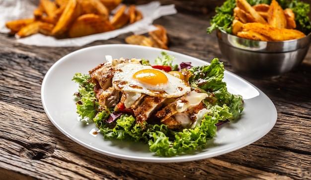 하얀 접시에 달걀과 소스를 곁들인 닭고기 샐러드와 소박한 나무, 한쪽에 웨지 감자가 있습니다.
