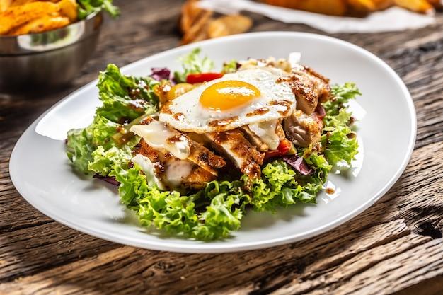 하얀 접시와 소박한 나무에 계란과 소스를 곁들인 닭고기 샐러드.