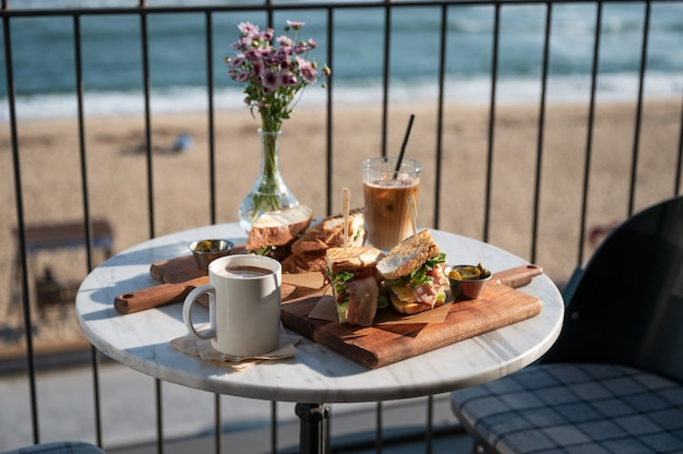 Chicken sandwich and iced coffee with hot cocoa and flower in vase on marble table in cafe near the beach at morning