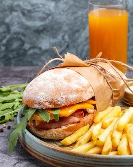 Куриный бутерброд с чеддером и руколой, подается с картофелем фри и апельсиновым соком