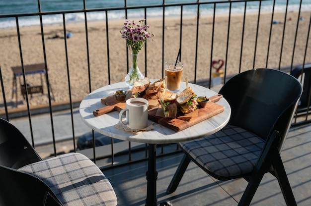 テラスでアイスコーヒーと花の装飾が施されたチキンサンドイッチ