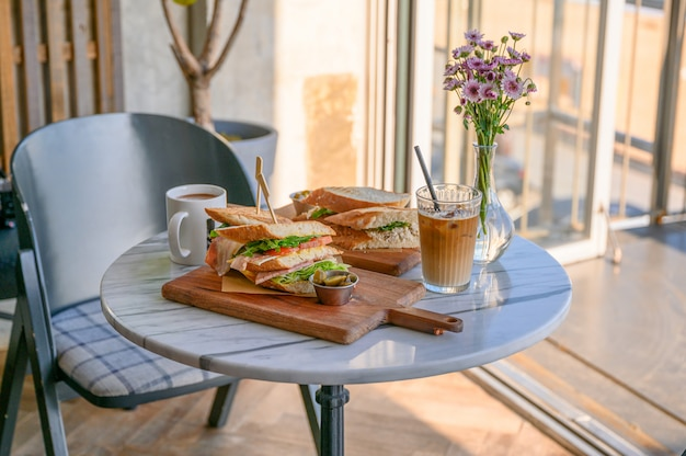 カフェのテーブルにアイスコーヒーと花瓶とチキンサンドイッチ