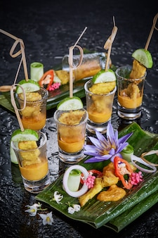Chicken satay in glass on dark.
