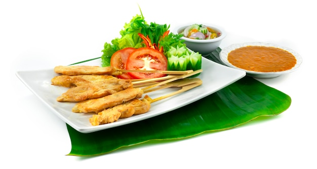 Куриный сатай или жареный цыпленок на шпажках, подаваемый в арахисовом соусе с чили, кисло-сладком соусе тайская еда, закуска, украшение блюда с резьбой из овощей, вид сбоку