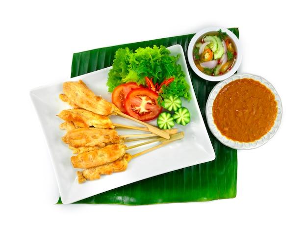 Куриный сатай или жареный цыпленок на шпажках, подаваемый в арахисовом соусе с чили, кисло-сладком соусе тайская еда, закуска, украшение блюда с овощами нарезкой сверху